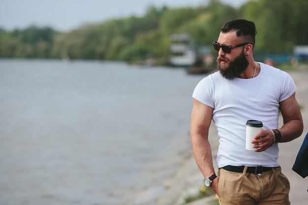 Uomo con una tazza di caffè che guarda la spiaggia