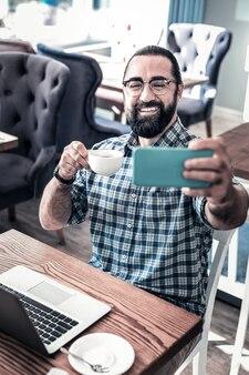 カップを持つ男。自分の写真を撮っている間彼のコーヒーのカップを保持している現代のひげを生やした黒髪の男