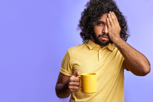 Man with cup of tea, curly arabic male needs some sleep, closing one eye posing at camera isolated over purple space