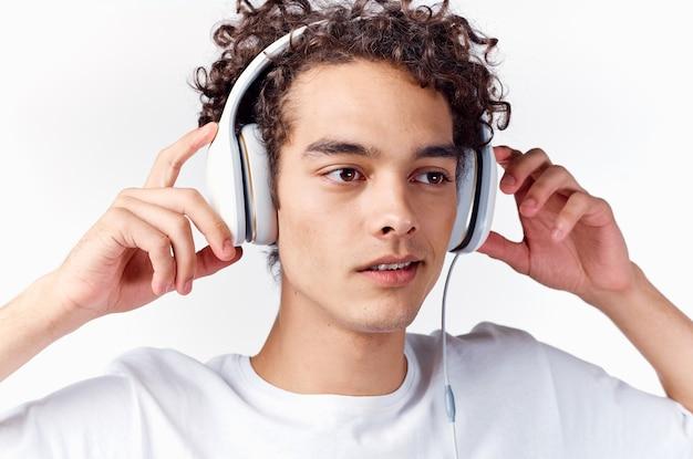 巻き毛とヘッドフォンで音楽を聴く男