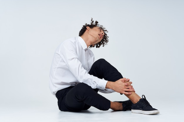 Man with curly hair in a classic suit and sneakers sits on the floor and side view copy space. high quality photo
