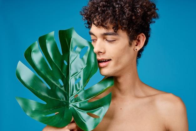Человек с вьющимися волосами, голые плечи, зеленые листья, экология