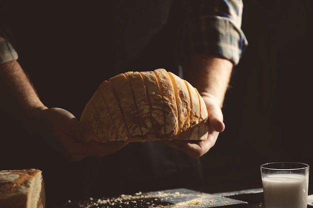 Man with cut bread in kitchen