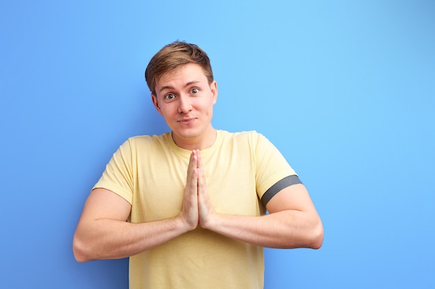Man with cute eyes, smiling while standing with praying or begging gesture and asking for favour. will you please go out with me tonight. isolated blue background