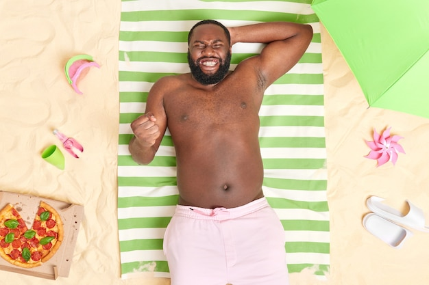 Man with dark skin clenches teeth and fist reacts on successful deal poses on striped towel at sandy beach spends summer vacation at seaside. nice vacation concept