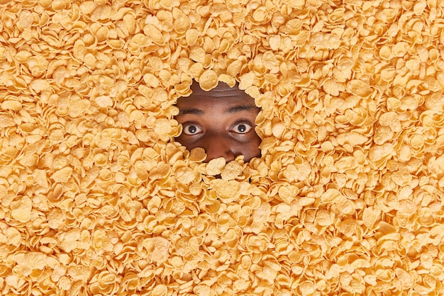 Man with dark skin shows only eyes drowned in cereals has krunchy snack for breakfast makes creative shot of food ingredients. overhead shot. cornflakes to eat