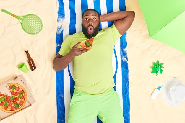 Man with dark skin stares impressed at camera lies at sandy beach eats delicious pizza dressed in green t shirt and shorts enjoys relaxation time lazy day