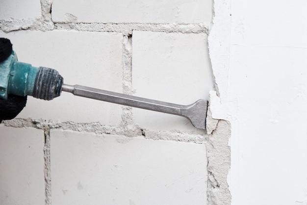 Человек с отбойным молотком снимает штукатурку со стены