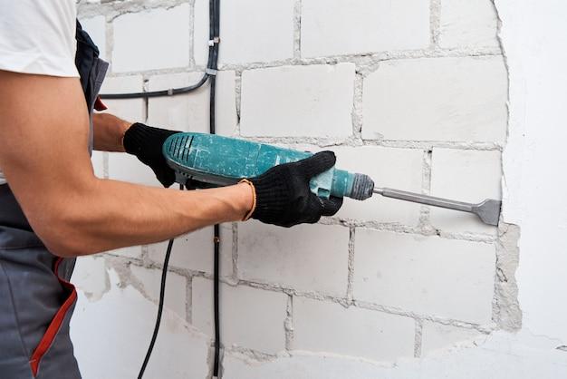 壁から漆喰を取り除く解体ハンマーを持つ男