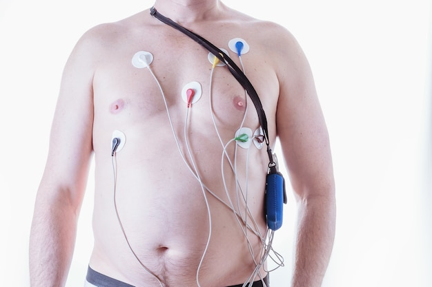 A man with a device for daily measurement of a cardiogram on a light background. the method of the halter. method of diagnosis of heart disease.