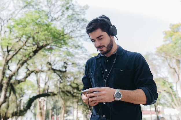Man with devices relaxing in park