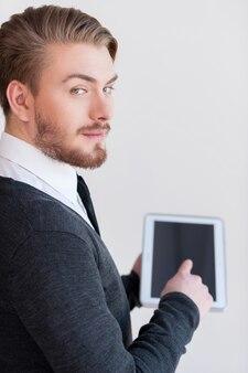Человек с цифровым планшетом. вид сзади красивого молодого человека, держащего цифровой планшет и смотрящего через плечо, стоя на сером фоне