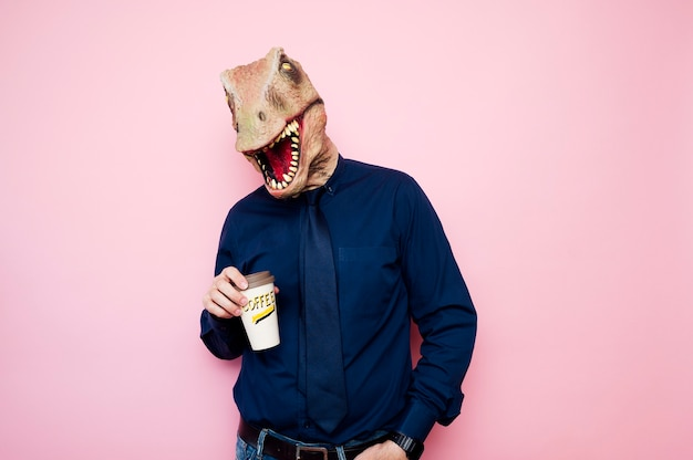 Man with dinosaur head holding a cup of coffee