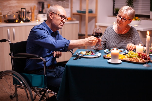 Man with disabilities having dinner with wife and clinking wine glass. wheelchair immobilized paralyzed handicapped man dining with wife at home, enjoying the meal
