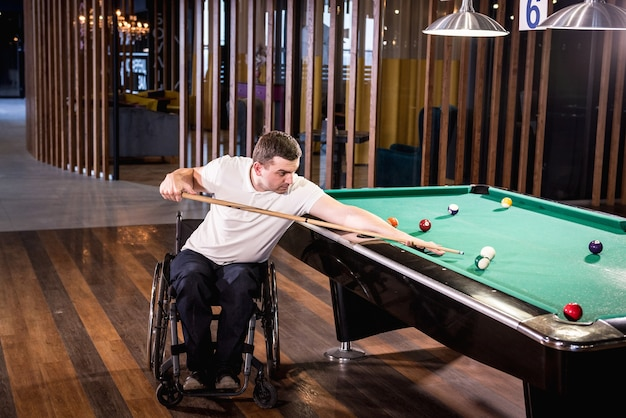 Man with disability in a wheelchair play billiards in the club