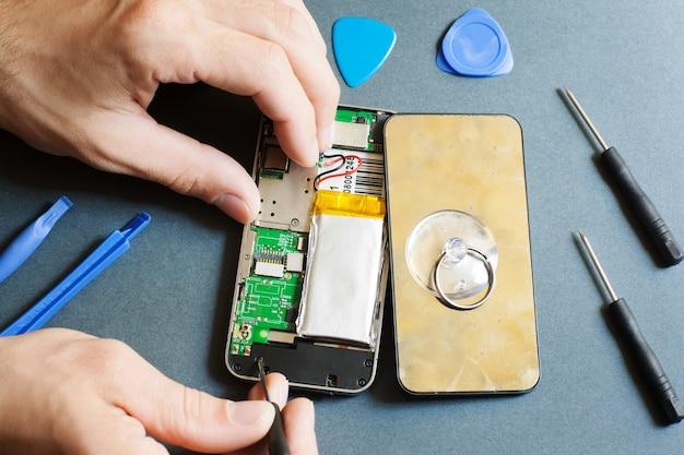 분해 된 휴대 전화 및 수리 도구를 가진 남자
