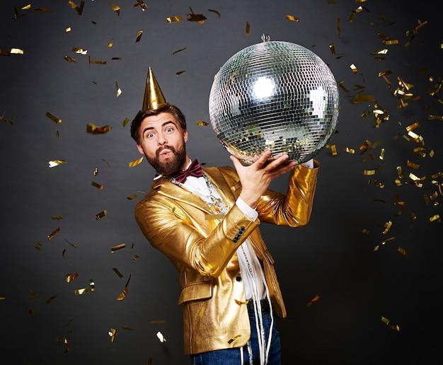 Человек с дискотечным шаром и шляпой на день рождения целуется