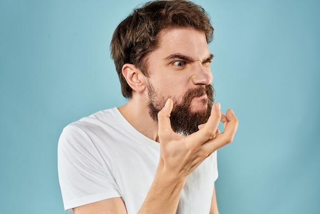 Человек с недовольным выражением лица жестикулирует руками студийный образ жизни синий фон