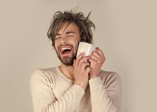 乱れた髪の男はコーヒーやミルクを飲みます。