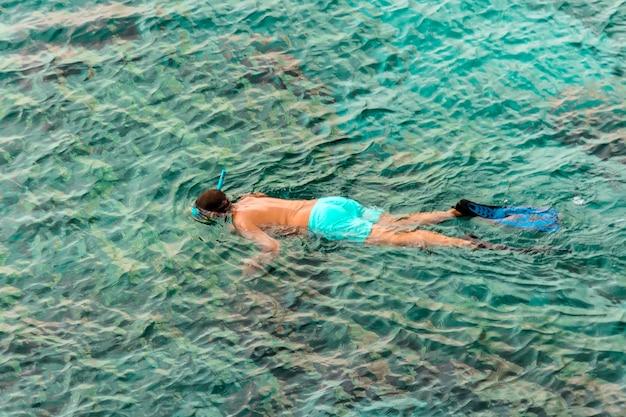 海、スポーツ、アクティビティ、自然の美しさ、アジア旅行、ランドマークでのダイビングマスクシュノーケリングの男。観光客は外洋でシュノーケリングをしています。海辺のリゾートでの休日