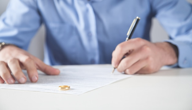 離婚契約と机の上の指輪を持つ男。離婚
