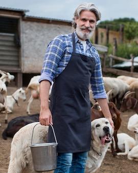 農場で犬を持つ男
