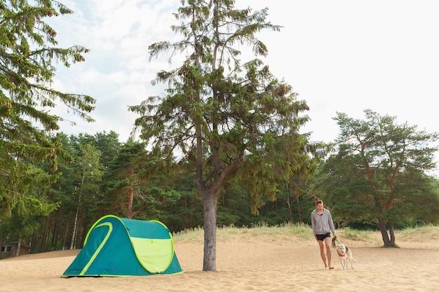 砂浜の木の下でテントで犬と男