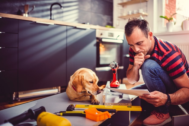 Man with dog checking blueprints while building kitchen cabinets