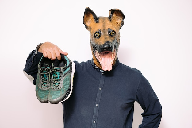 Man with dog mask holding a pair of running shoes