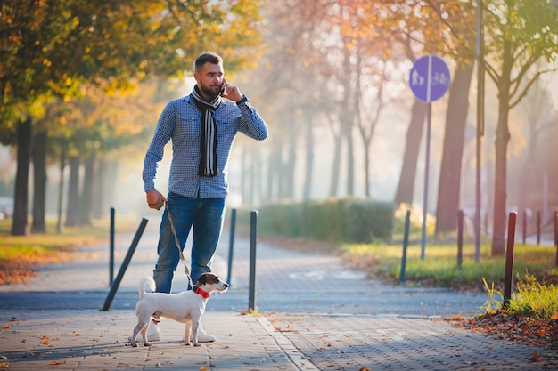Man with dog walking at autumn season alley.
