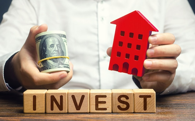 A man with dollars and a house figurine and the word invest real estate financial investment