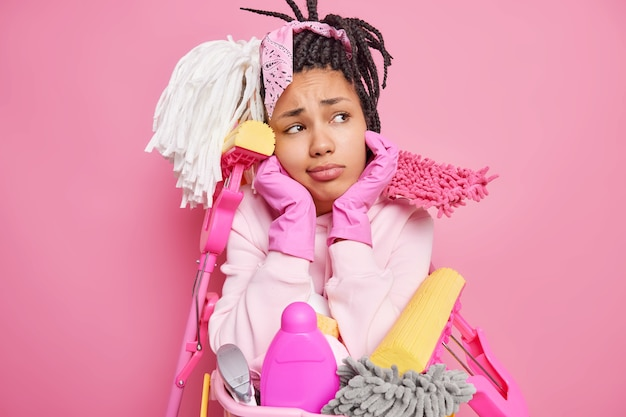 Man with dreadlocks holds chin surrounded by cleaning supplies holds near basin of laundry isolated on pink