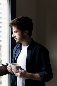 Man with drink looking out office window