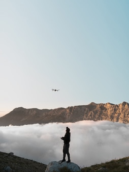 A man with a drone in the mountains flying behind the clouds