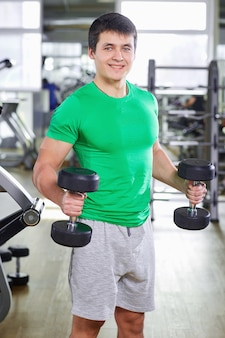 A man with dumbbells doing exercises in the gym