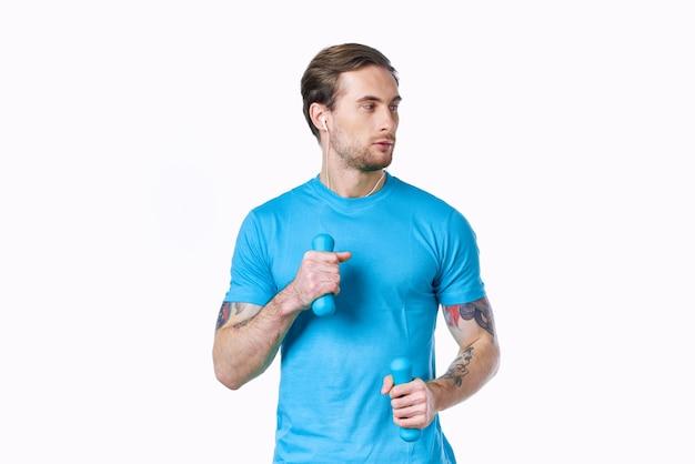 Человек с гантелями в синей футболке на светлом фоне, глядя в сторону обрезанный вид