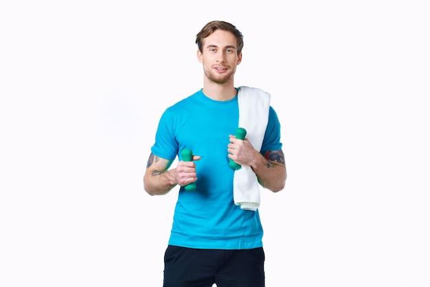 手にダンベルを持つ男トレーニングフィットネス運動明るい背景