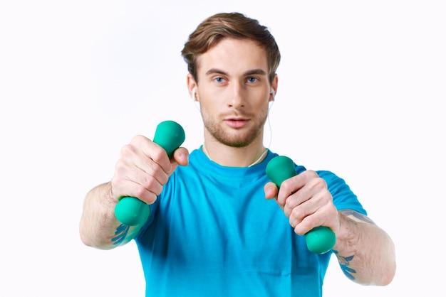 彼の手にダンベルを持つ男青いtシャツエクササイズフィットネスヘッドフォン