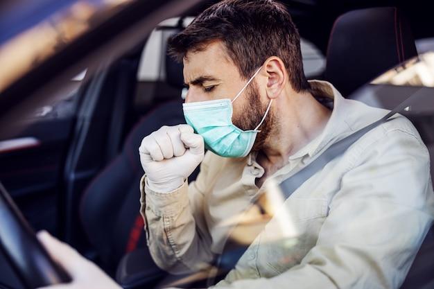 전자 마스크와 장갑 차 기침을 운전하는 남자. 감염 예방 및 전염병 통제. 세계 대유행. 안전 유지.