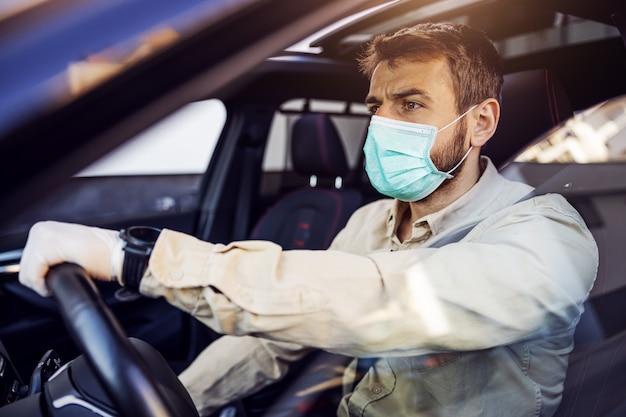 Человек с маской e и перчатками за рулем автомобиля. профилактика инфекций и борьба с эпидемиями. мировая пандемия. оставайся в безопасности.