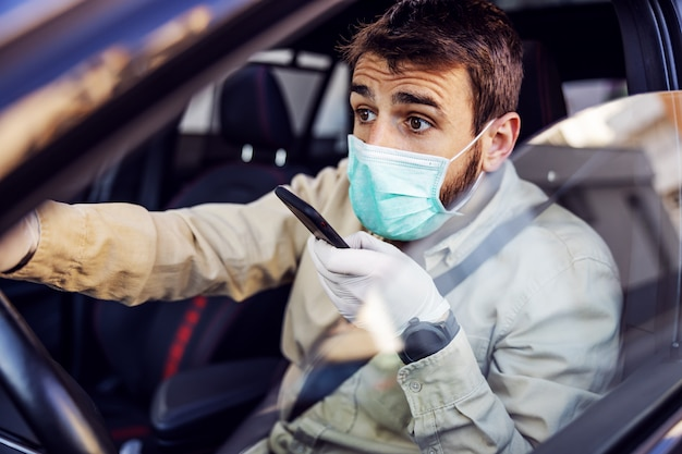 전자 마스크와 장갑 휴대 전화 스마트 폰에 얘기하는 차를 운전하는 남자. 감염 예방 및 전염병 통제. 세계 대유행. 안전 유지.