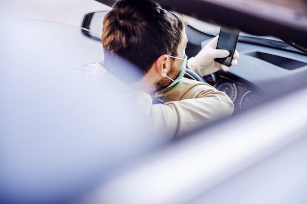 전자 마스크와 스마트 폰 휴대 전화에 입력하는 차를 운전하는 장갑 남자. 감염 예방 및 전염병 통제. 세계 대유행. 안전 유지.