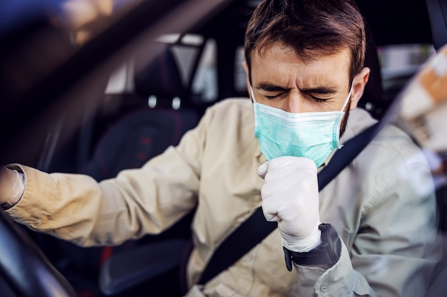 Man with e mask and gloves driving a car coughing. infection prevention and control of epidemic. world pandemic. stay safe.