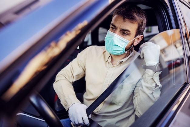 Man with e mask and gloves driving a car. infection prevention and control of epidemic. world pandemic. stay safe.