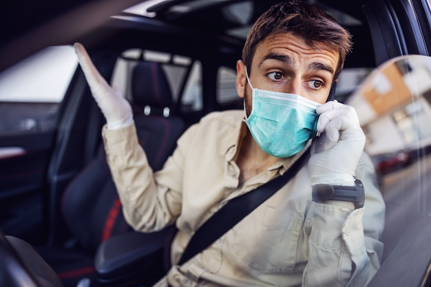 Man with e mask and gloves driving a car talking on mobile phone smartphone. infection prevention and control of epidemic. world pandemic. stay safe.