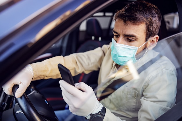 Man with e mask and gloves driving a car typing at smartphone mobile phone. infection prevention and control of epidemic. world pandemic. stay safe.