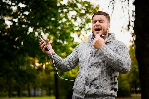Man with earphones in ears singing in the park
