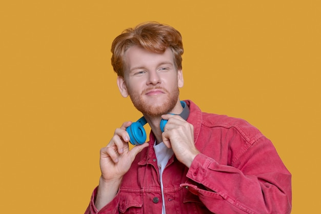 Man with earphones. young ginger man in red shirt with blue earphones