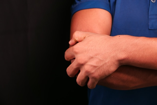 Man with elbow pain isolated in black. pain relief concept.