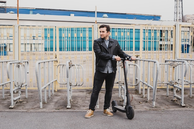 フェンスの上に折衷的なスクーターを持つ男